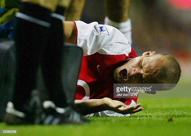 Arsenal's Fredrik Ljungberg lets out a yell as he is treated after being fouled by Newcaslte's Laurent Robert during their match 26 September 2003 at...
