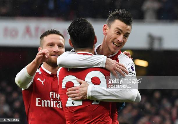 Arsenal's French defender Laurent Koscielny celebrates after scoring their third goal with Arsenal's Swiss midfielder Granit Xhaka during the English...