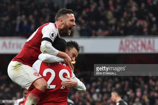 Arsenal's French defender Laurent Koscielny celebrates after scoring their third goal with Arsenal's Swiss midfielder Granit Xhaka and Arsenal's...
