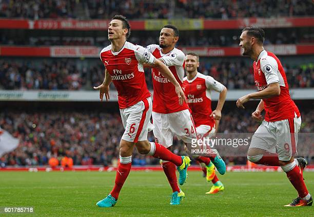 Arsenal's French defender Laurent Koscielny celebrates with teammates after scoring their first goal with an overhead kick during the English Premier...