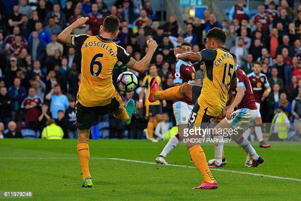Arsenal's French defender Laurent Koscielny deflects the ball into the net from English midfielder Alex OxladeChamberlain's shot as Arsenal score a...