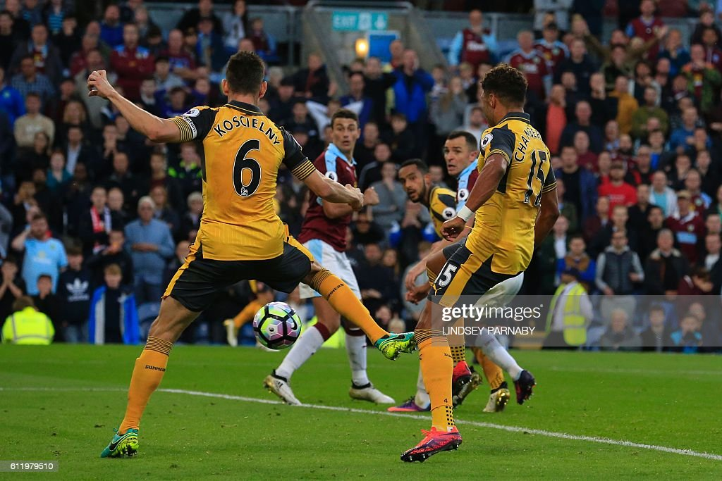 Arsenal's French defender Laurent Koscielny (L) deflects the ball into the net from English midfielder Alex Oxlade-Chamberlain's shot as Arsenal score a last minute winning goal during the English Premier League football match between Burnley and Arsenal at Turf Moor in Burnley, north west England on October 2, 2016. Arsenal won the game 1-0. / AFP / Lindsey PARNABY / RESTRICTED TO EDITORIAL USE. No use with unauthorized audio, video, data, fixture lists, club/league logos or 'live' services. Online in-match use limited to 75 images, no video emulation. No use in betting, games or single club/league/player publications. /
