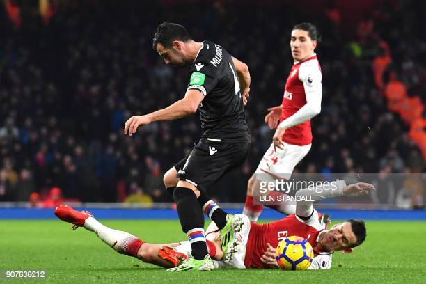 Arsenal's French defender Laurent Koscielny tackles Crystal Palace's Serbian midfielder Luka Milivojevic during the English Premier League football...