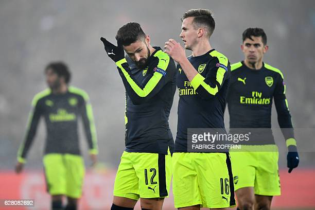 Arsenal's French forward Olivier Giroud and Arsenal's English defender Rob Holding react at the end of the UEFA Champions league Group A football...