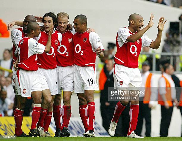 Arsenal's French forward Thierry Henry celebrates as teammate Robert Pires is mobbed by Patrick Vieira Ashley Cole Gilberto Silva and Dennis Bergkamp...