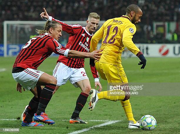 Arsenal's French forward Thierry Henry fights for the ball with AC Milan's french defender Philippe Mexes during the UEFA Champions League round of...