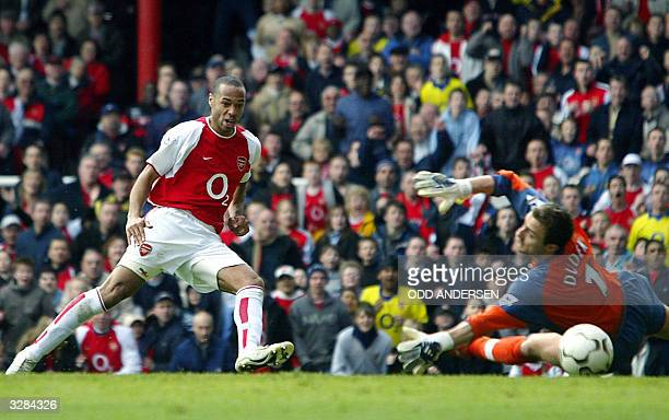 Arsenal's French forward Thierry Henry puts the ball beyond Liverpool goalie Jerzy Dudek for his second goal of the day during their premier league...
