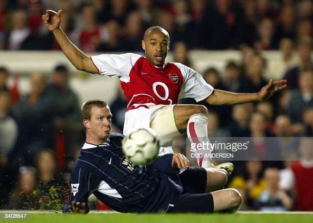 Arsenal's French forward Thierry Henry shoots past Steven Caldwell of Leeds during their premier league clash at Highbury in London 16 April 2004...