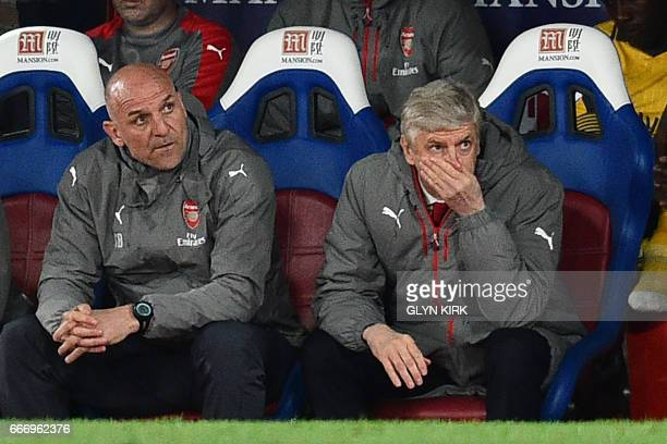 Arsenal's French manager Arsene Wenger and assistant Steve Bould gesture in their seats during the English Premier League football match between...