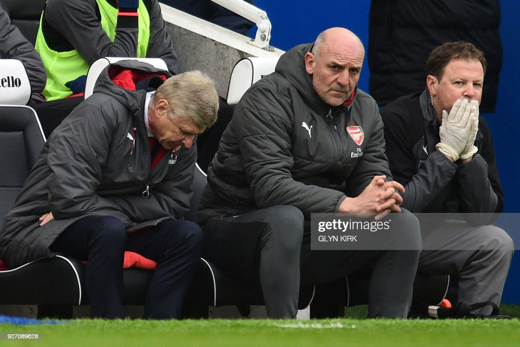 Arsenal's French manager Arsene Wenger (L), Arsenal's assistant manager Steve Bould (C) and Head of medical services Colin Lewin react on in their seats as Brighton lead 2-0, during the English Premier League football match between Brighton and Hove Albion and Arsenal at the American Express Community Stadium in Brighton, southern England on March 4, 2018. / AFP PHOTO / Glyn KIRK / RESTRICTED TO EDITORIAL USE. No use with unauthorized audio, video, data, fixture lists, club/league logos or 'live' services. Online in-match use limited to 75 images, no video emulation. No use in betting, games or single club/league/player publications. /