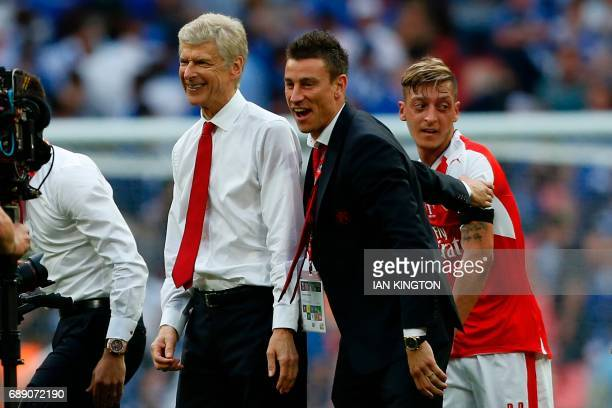 Arsenal's French manager Arsene Wenger celebrates with Arsenal's French defender Laurent Koscielny and Arsenal's German midfielder Mesut Ozil on the...