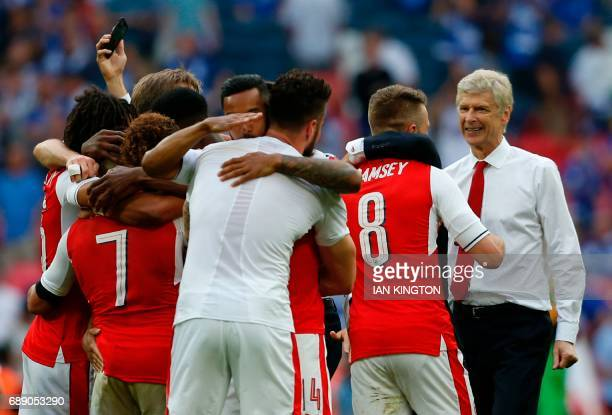 Arsenal's French manager Arsene Wenger celebrates with his players on the pitch after the English FA Cup final football match between Arsenal and...