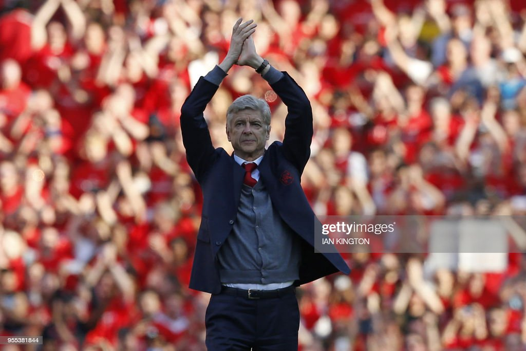 TOPSHOT - Arsenal's French manager Arsene Wenger gestures to supporters on the pitch after the English Premier League football match between Arsenal and Burnley at the Emirates Stadium in London on May 6, 2018. - Arsene Wenger bids farewell to a stadium he helped to build in more ways than one when he leads Arsenal at the Emirates for the final time at home to Burnley on Sunday. Wenger's final season after 22 years in charge is destined to end in disappointment after Thursday's Europa League semi-final exit. (Photo by Ian KINGTON / IKIMAGES / AFP) / RESTRICTED TO EDITORIAL USE. No use with unauthorized audio, video, data, fixture lists, club/league logos or 'live' services. Online in-match use limited to 45 images, no video emulation. No use in betting, games or single club/league/player publications. /