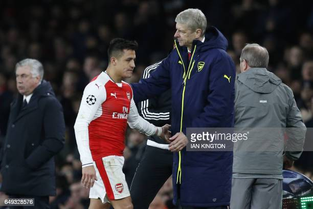 Arsenal's French manager Arsene Wenger greets Arsenal's Chilean striker Alexis Sanchez after he is substituted during the UEFA Champions League last...