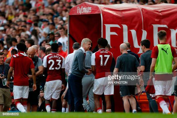 Arsenal's French manager Arsene Wenger greets staff at the mouth of the player's tunnel at the end of the English Premier League football match...