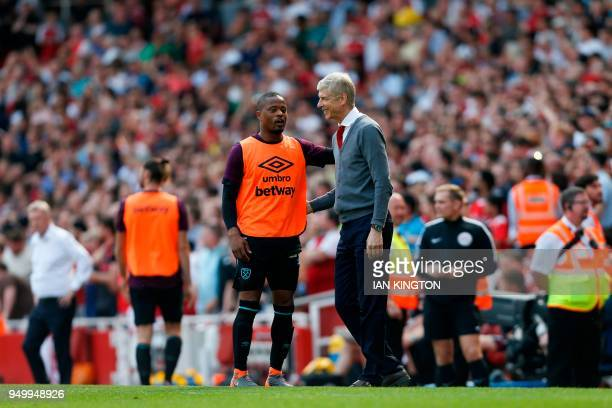Arsenal's French manager Arsene Wenger greets West Ham United's French defender Patrice Evra on the touch line during the English Premier League...