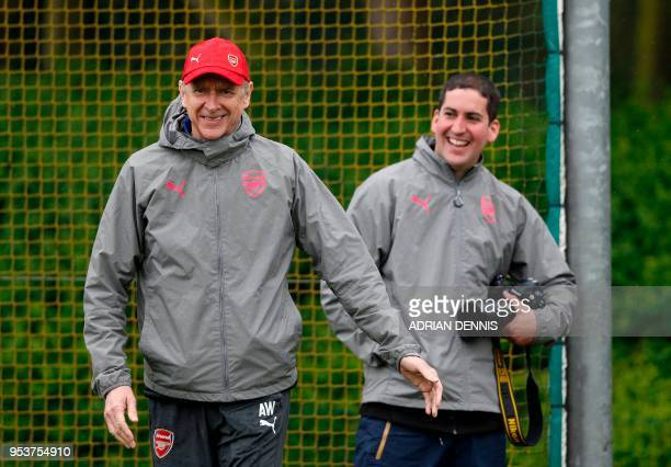 Arsenal's French manager Arsene Wenger jokes with David Price, club photographer during a training session at the club's complex in London Colney on...