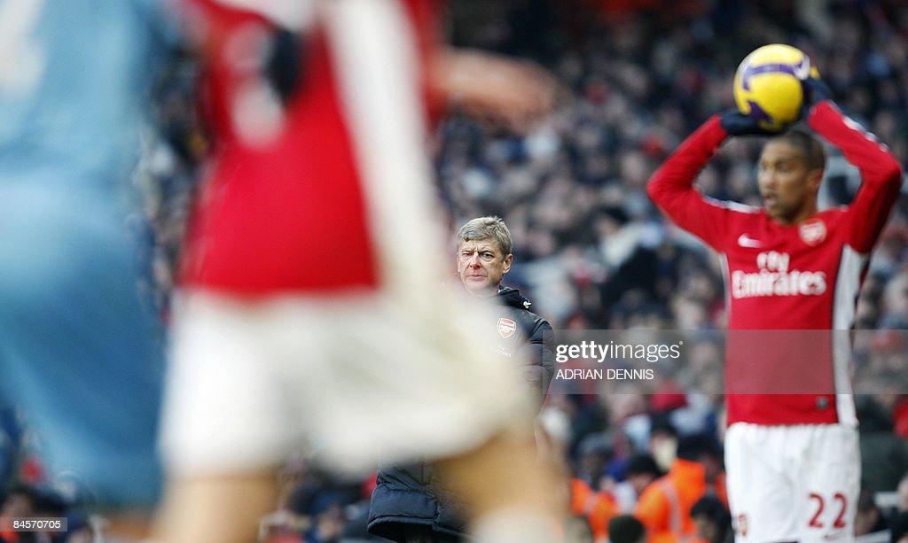 Arsenal's French Manager Arsene Wenger (C back) looks on from the sidelines as Gael Clichy (R) prepares to take a throw-in against West Ham during the Premiership match at The Emirates Stadium in London on January 31, 2009. The game ended 0-0. AFP PHOTO / Adrian Dennis FOR EDITORIAL USE ONLY Additional licence required for any commercial/promotional use or use on TV or internet (except identical online version of newspaper) of Premier League/Football League photos. Tel DataCo +44 207 2981656. Do not alter/modify photo.