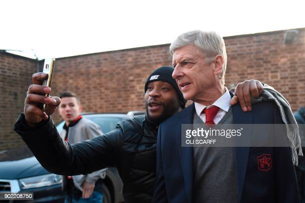 Arsenal's French manager Arsene Wenger poses for a selfi with a fan as he arrives for the English FA Cup third round football match between...