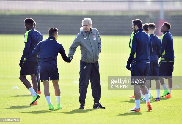 Arsenal's French manager Arsene Wenger shakes hands with Chilean striker Alexis Sanchez during a training session ahead of their UEFA Champions...