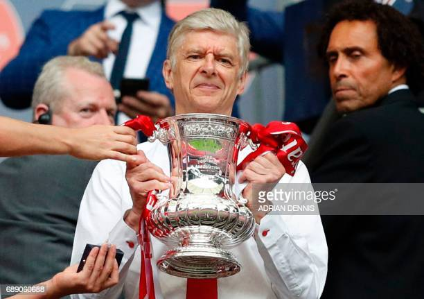 Arsenal's French manager Arsene Wenger smiles as he holds the FA Cup trophy after their win over Chelsea in the English FA Cup final football match...