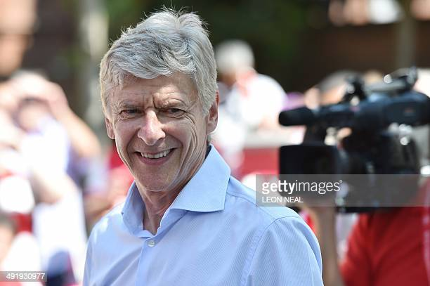 Arsenal's French manager Arsene Wenger smiles durin g their victory parade in London on May 18 following their win in the English FA Cup final...