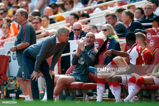 Arsenal's French manager Arsene Wenger talks with Arsenal's English midfielder Ainsley MaitlandNiles as the player prepares to come on to replace the...