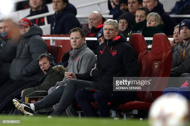 Arsenal's French manager Arsene Wenger watches from his seat during the second leg of the Europa League Round of 32 football match between Arsenal...