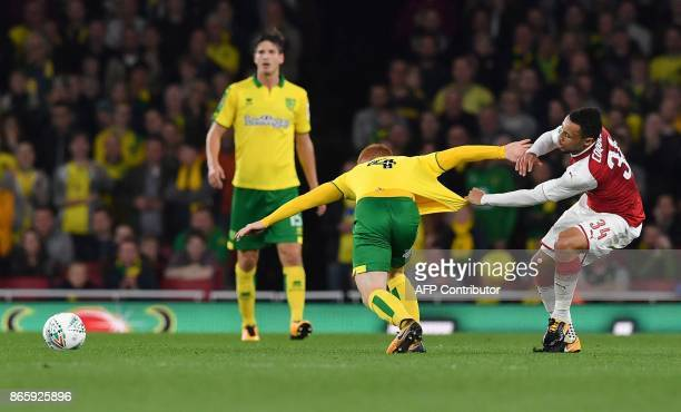 Arsenal's French midfielder Francis Coquelin pulls the shirt of Norwich City's English midfielder Harrison Reed during the English League Cup fourth...
