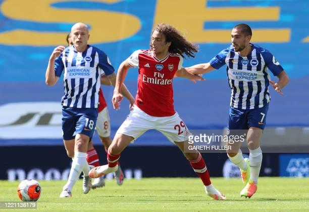 Arsenal's French midfielder Matteo Guendouzi fights for the ball with Brighton's French striker Neal Maupay during the English Premier League...