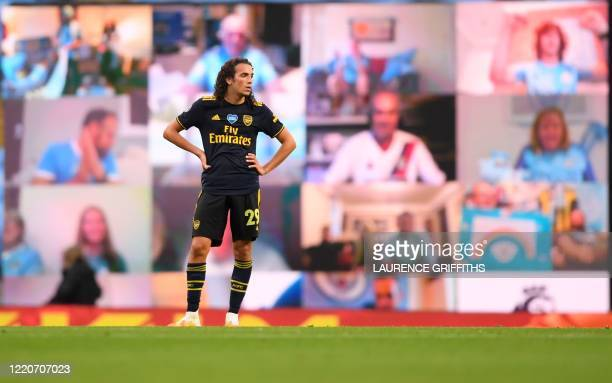 Arsenal's French midfielder Matteo Guendouzi reacts as he stands in front of a screen showing Manchester City fans celebrating after Manchester...