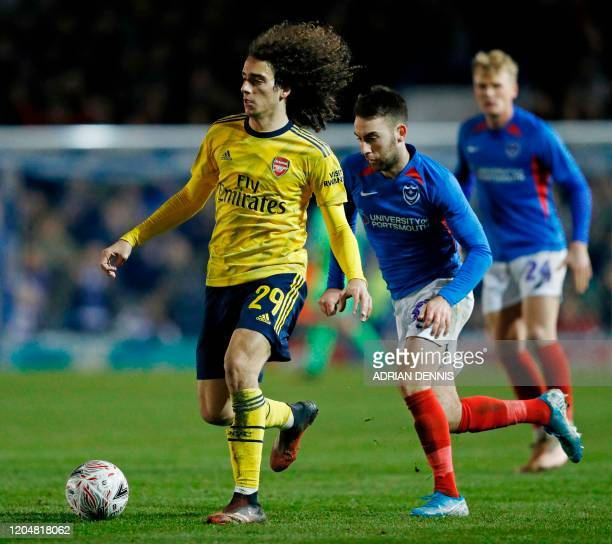 Arsenal's French midfielder Matteo Guendouzi runs away from Portsmouth's English midfielder Ben Close during the English FA Cup fifth round football...