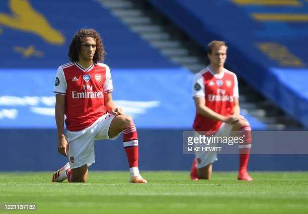 Arsenal's French midfielder Matteo Guendouzi takes a knee to show support for the Black Lives Matter movement and as a protest against racism ahead...