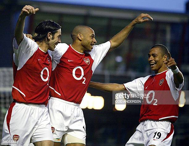 Arsenal's French midfielder Robert Pires celebrates his goal against Leeds with French forward Thierry Henry and Brazilian Gilberto during their...