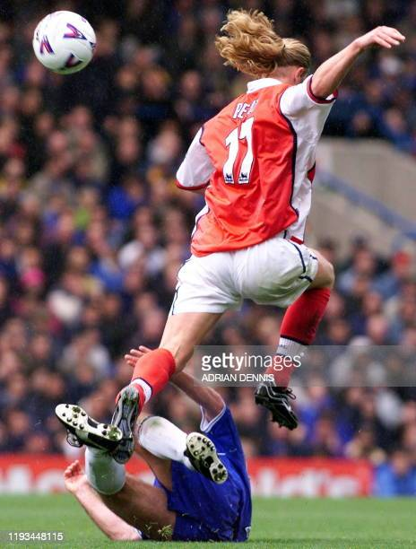 Arsenal's French player Emmanuel Petit goes airborne against Chelsea player during the premiership match at Stamford Bridge 23 October 1999....