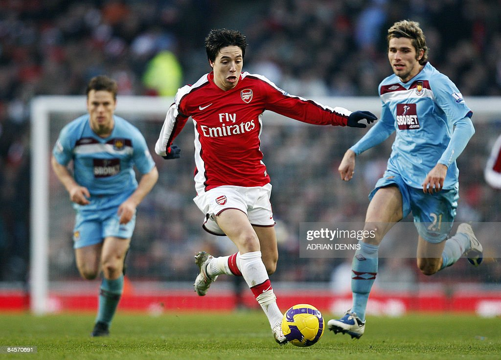 Arsenal's French player Samir Nasri (C) runs with the ball, pursued by West Ham's Swiss player Valon Behrami (R), during their Premiership match at The Emirates Stadium in London on January 31, 2009. The game ended in a 0-0 tie. AFP PHOTO / Adrian Dennis --- FOR EDITORIAL USE ONLY Additional licence required for any commercial/promotional use or use on TV or internet (except identical online version of newspaper) of Premier League/Football League photos. Tel DataCo +44 207 2981656. Do not alter/modify photo.