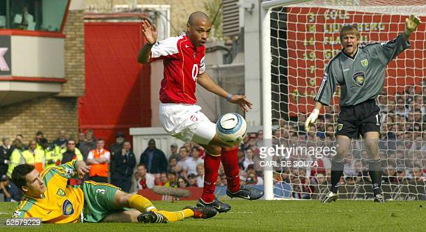 Arsenal's French player Thierry Henry controls the ball past Norwich's Gary Holt as goalkeeper Robert Green looks on during their premiership match,...