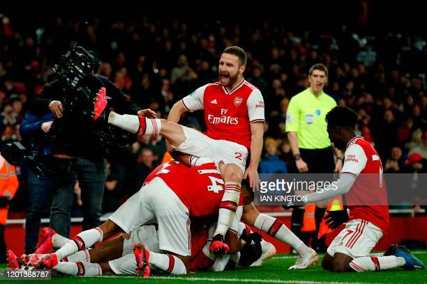 Arsenal's French striker Alexandre Lacazette celebrates with Arsenal's German defender Shkodran Mustafi and teammates after scoring their fourth goal...