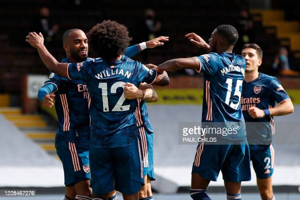 Arsenal's French striker Alexandre Lacazette celebrates with Arsenal's Brazilian midfielder Willian after scoring the opening goal during the English...