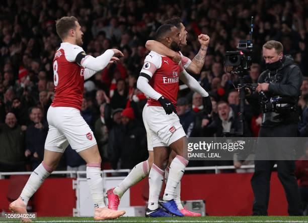 Arsenal's French striker Alexandre Lacazette celebrates with teammates after scoring his team's first goal during the English Premier League football...