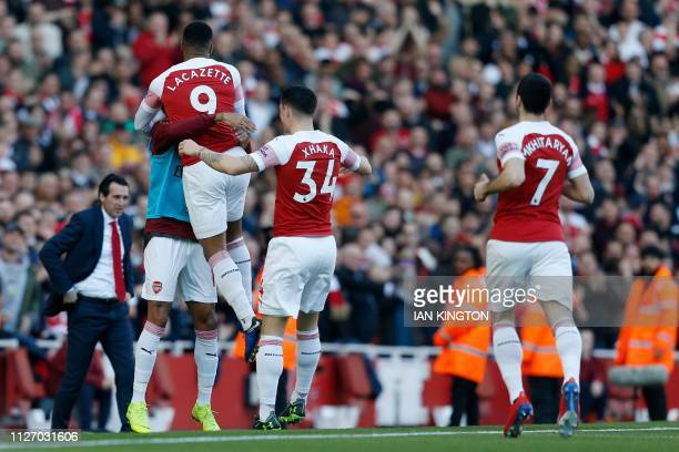 Arsenal's French striker Alexandre Lacazette celebrates with teammates after scoring during the English Premier League football match between Arsenal...
