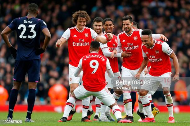 Arsenal's French striker Alexandre Lacazette celebrates with teammates after scoring the opening goal of the English Premier League football match...