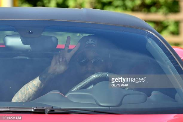 Arsenal's French striker Alexandre Lacazette gestures as he arrives at Arsenal's Colney training centre north of London on May 20 2020 as training...