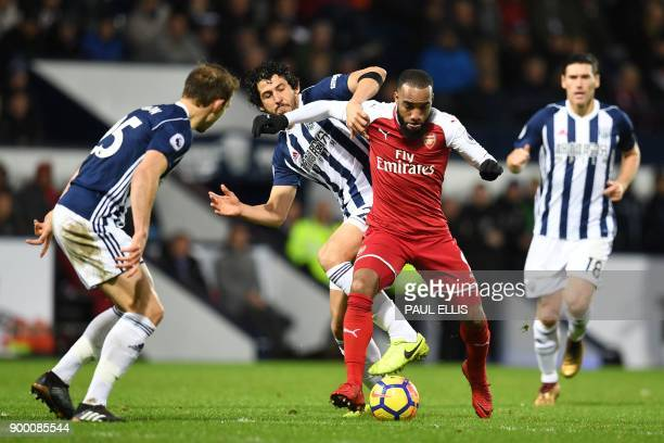 Arsenal's French striker Alexandre Lacazette is tackled by West Bromwich Albion's Egyptian defender Ahmed Hegazy during the English Premier League...