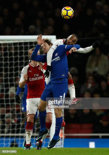 Arsenal's French striker Alexandre Lacazette jumps for the ball with Chelsea's Spanish defender Marcos Alonso during the English Premier League...