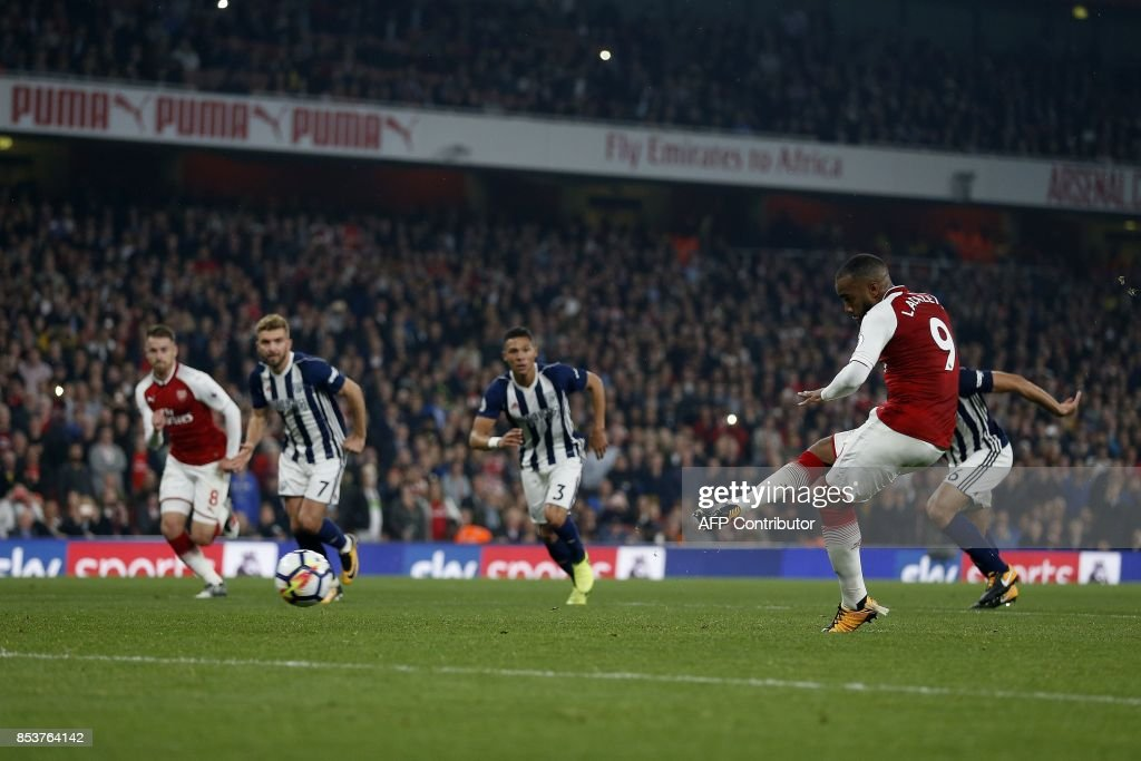 TOPSHOT - Arsenal's French striker Alexandre Lacazette shoots from the penalty spot to score his team's second goal during the English Premier League football match between Arsenal and West Bromwich Albion at the Emirates Stadium in London on September 25, 2017. / AFP PHOTO / Ian KINGTON / RESTRICTED TO EDITORIAL USE. No use with unauthorized audio, video, data, fixture lists, club/league logos or 'live' services. Online in-match use limited to 75 images, no video emulation. No use in betting, games or single club/league/player publications. /