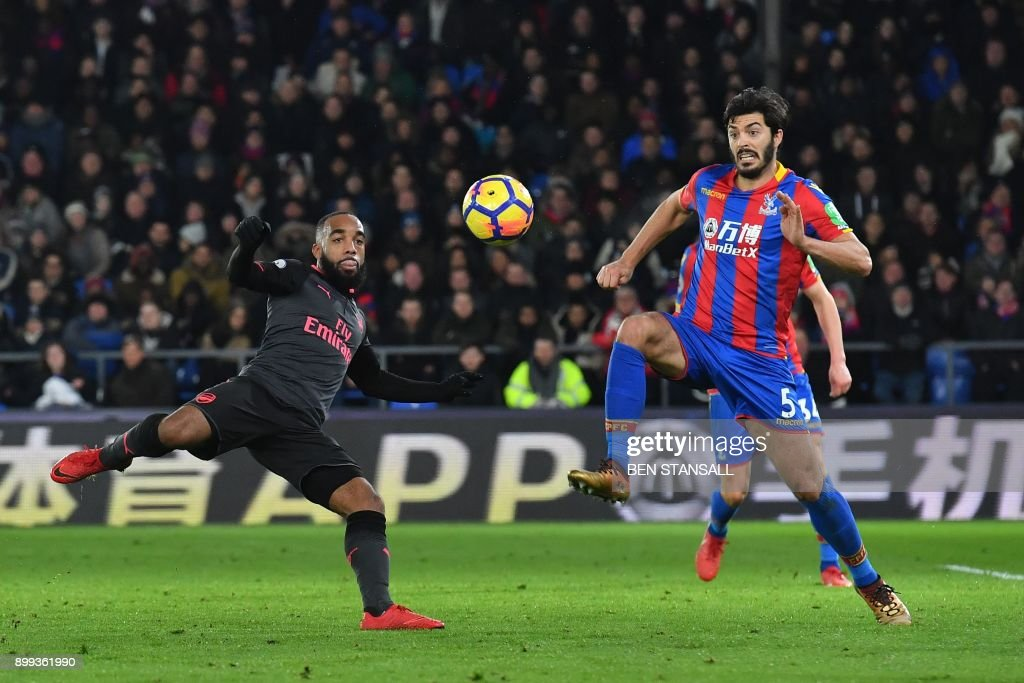 TOPSHOT - Arsenal's French striker Alexandre Lacazette (L) vies with Crystal Palace's English defender James Tomkins during the English Premier League football match between Crystal Palace and Arsenal at Selhurst Park in south London on December 28, 2017. / AFP PHOTO / Ben STANSALL / RESTRICTED TO EDITORIAL USE. No use with unauthorized audio, video, data, fixture lists, club/league logos or 'live' services. Online in-match use limited to 75 images, no video emulation. No use in betting, games or single club/league/player publications. /