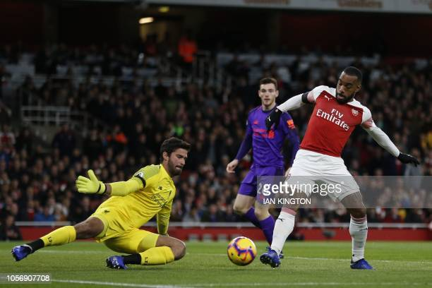 Arsenal's French striker Alexandre Lacazette vies with Liverpool's Brazilian goalkeeper Alisson Becker during the English Premier League football...