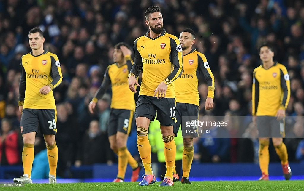Arsenal's French striker Olivier Giroud (C) and teammates react after Everton's English-born Welsh defender Ashley Williams scored his teams's second goal during the English Premier League football match between Everton and Arsenal at Goodison Park in Liverpool, north west England on December 13, 2016. Everton won the match 2-1. / AFP / Paul ELLIS / RESTRICTED TO EDITORIAL USE. No use with unauthorized audio, video, data, fixture lists, club/league logos or 'live' services. Online in-match use limited to 75 images, no video emulation. No use in betting, games or single club/league/player publications. /