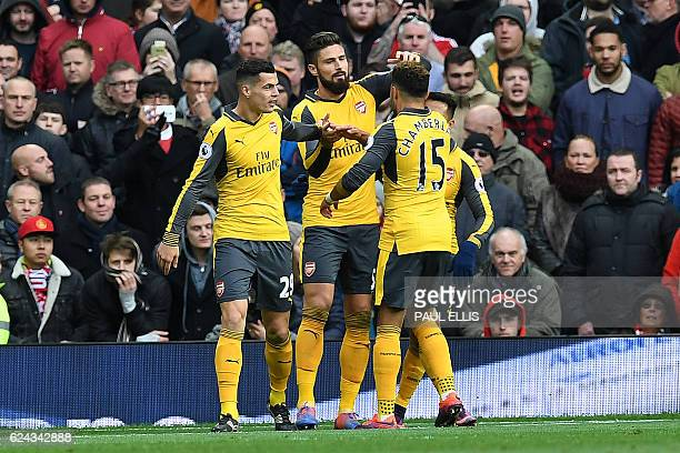 Arsenal's French striker Olivier Giroud celebrates scoring his team's first goal with Arsenal's English midfielder Alex OxladeChamberlain Arsenal's...